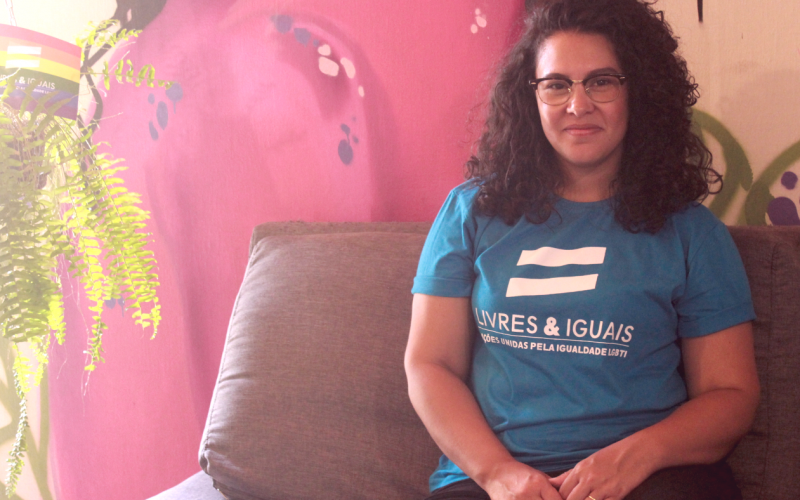 Foto da Ananda sentada num sofá encostado na parede. Ela está com camiseta da campanha Livres e Iguais da ONU.