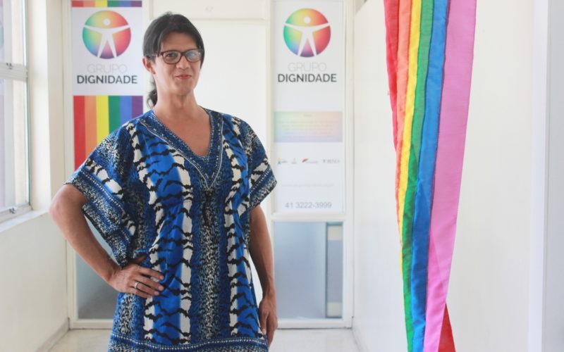 Foto da Rafaelly Wiest em frente a porta de entrada do escritório do Grupo Dignidade em Curitiba, Paraná. Ela está em pé ao fundo vê-se a porta com a logo do Grupo Dignidade e uma bandeira LGBTI+ pendurada na parede